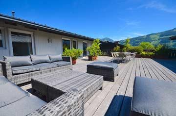 Ferienwohnung Zell am See für Gruppen - die Terrasse zwischen den beiden Hausflügeln im Sommer