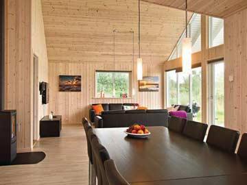 Wohnzimmer mit großem Esstisch und Kaminofen
