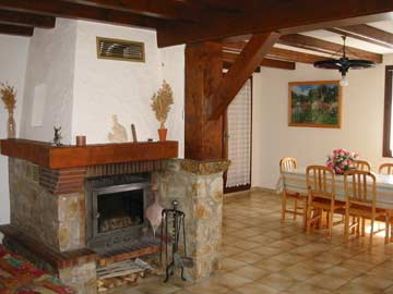 Großer Wohnraum mit Esstisch und offenem Kamin