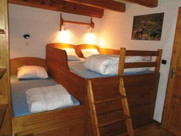 Blick in die Schlafzimmer: das 4-Bett-Zimmer mit dem erhöht liegenden frz. Bett und 2 weiteren Einzelbetten