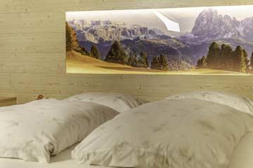 Indirekte Beleuchtung an der Stirnseite der Betten mit herrlichen Dolomitenmotiven