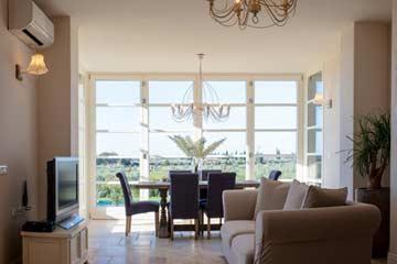 Wohnzimmer mit großen Fenstern am Esstisch
