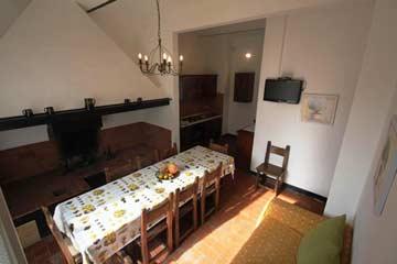 Fewo 5: Speise- und Wohnzimmer mit großem Esstisch, Sofa und Kamin
