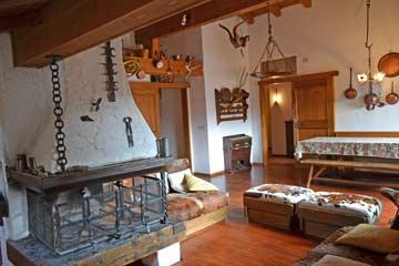 Schöner, uriger Wohnraum mit offenem Kamin und Esstisch