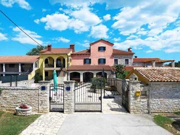 Außenansicht des Ferienhauses mit umzäuntem Grundstück