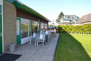 Terrasse mit Tischen und Stühlen (Im Hintergrund Haus NLZE/III/7)