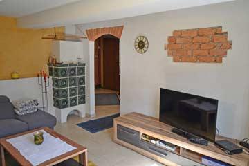 Wohnzimmer mit TV und Kachelofen