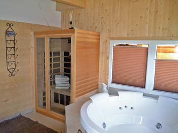 Badezimmer mit Whirlpool und Infrarotkabine