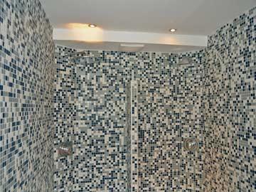 Durch das Mosaik auf dem Foto schwierig zu erkennen: die große Raindance-Dusche im Wellnessbereich, rechts Wasserschwalldusche