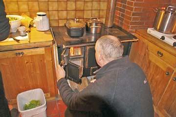Holzofen in der Küche: urgemütliche Wärme und Kochen wie zu Großmutters Zeiten (daneben auch Elektro-Platten)