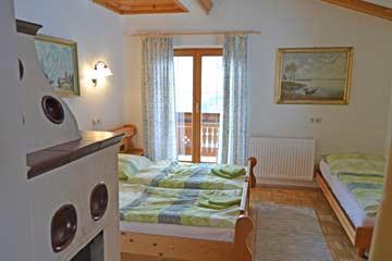 das mit Vorhang vom Wohnraum abgetrennte 3-Bett-Zimmer mit Kachelofen und Balkon