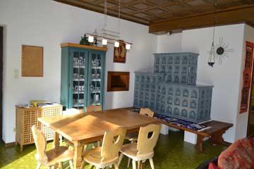 Esstisch und Kachelofen im Wohnraum