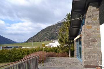 Terrasse im Frühling bei der Schneeschmelze mit Blick zur Talstation der Bergbahn Kals (links), rechts noch Schneereste auf der Skipiste